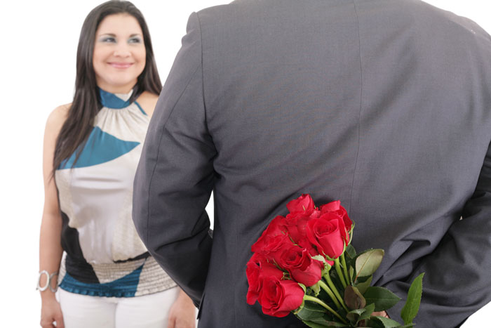man hiding red rose bouquet behind his back