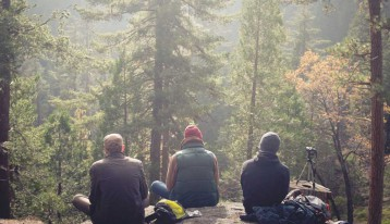 group of young men resting during hike in forest