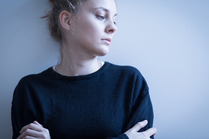 young depressed woman in black sweater with arms crossed