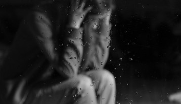 upset woman seen through glass with rain on it - black and white