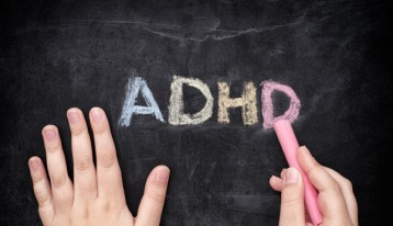 ADHD written in colored chalk on black chalkboard