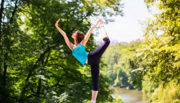 woman doing advanced yoga in a park near a river