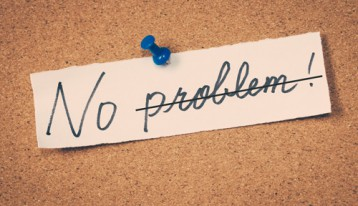 scrap of paper pinned to corkboard that says 'No Problem' with 'problem' crossed out
