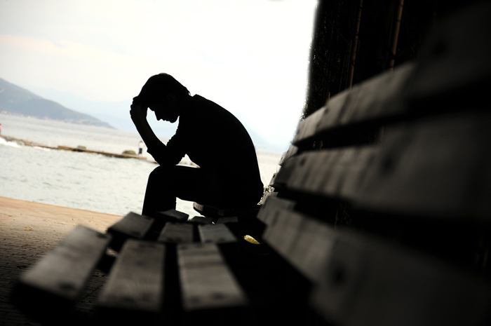 depressed man on bench near ocean