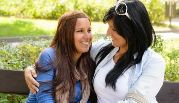 mom with teen daughter smiling and hugging on park bench