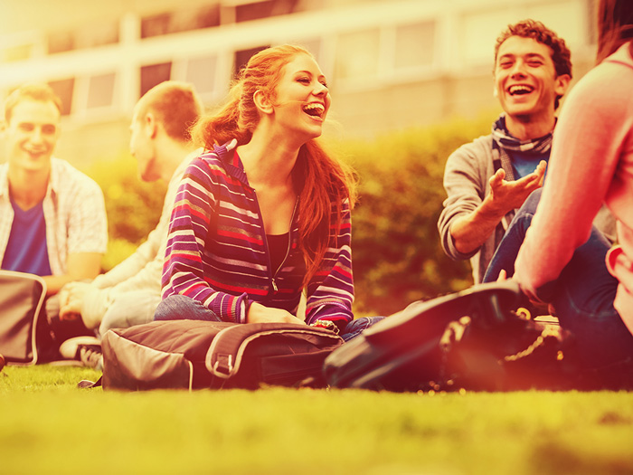 college students smiling and sitting together on lawn
