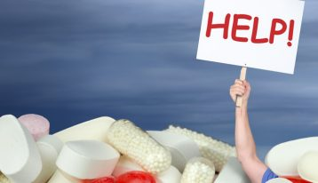 chemical dependency - person holding help sign with pills - ranch at dove tree