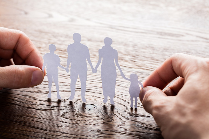 hands holding white paper cutout of family