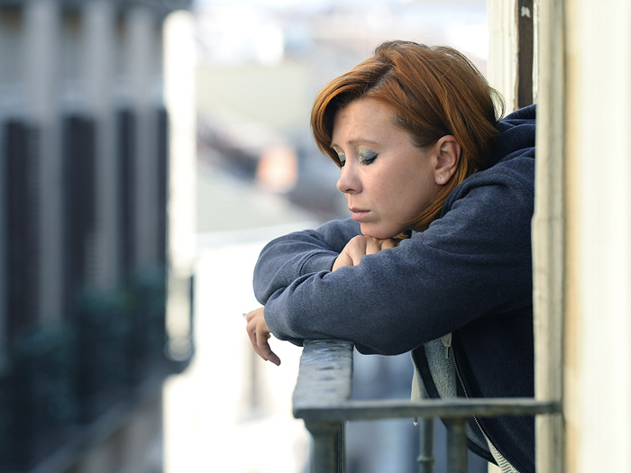 depressed woman on balcony with eyes closed