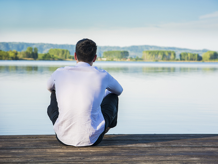 man sitting at the edge of a lake with back to camera