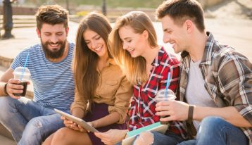 What Is a Collegiate Residential Drug Abuse Program? - 4 college students visiting outside looking at ipad