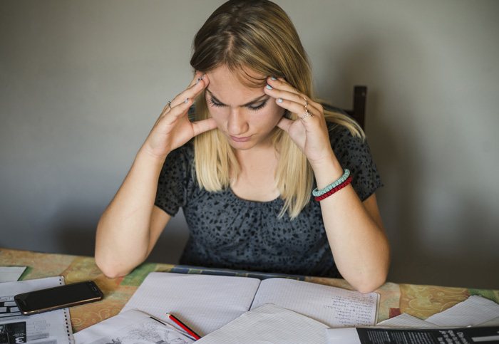 stressed blonde girl student studying at desk