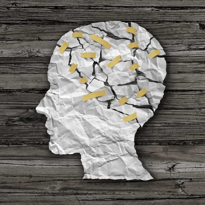 Drug Addictions and How They Affect the Human Brain - paper silhouette taped together head on wood background