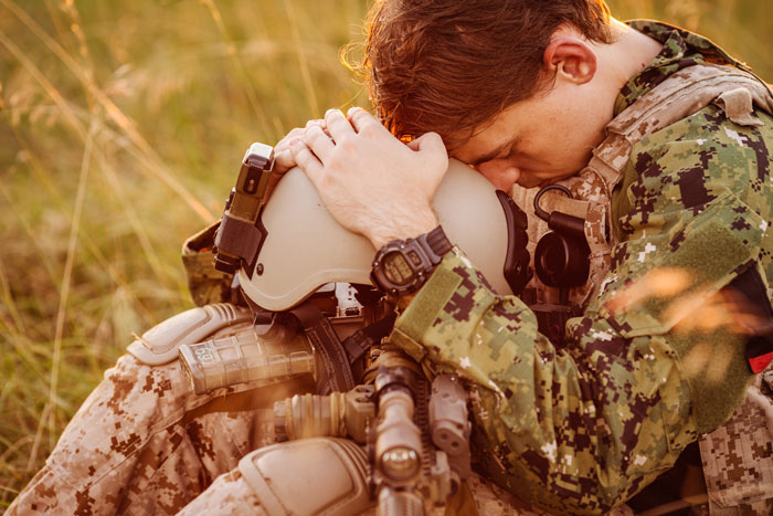 Veterans-and-Drug-and-Alcohol-Addiction - US soldier depressed sitting in field
