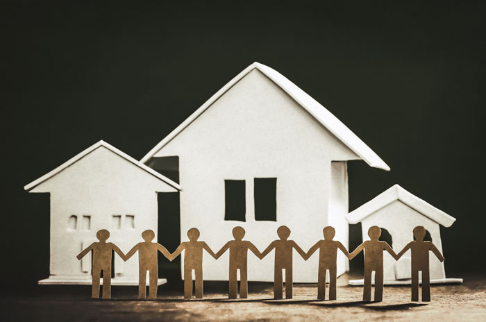 Benefits-of-Transitional-Living-After-Addiction-Treatment - cut outs holding hands, houses