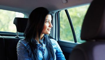 woman in back seat of car smiling looking out window