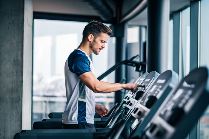 man on treadmill at gym - stress