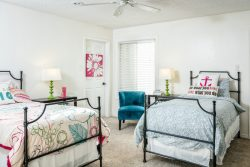 bright white bedroom with 2 double beds and ceiling fan