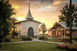 front view of lovely small chapel on manicured grounds during sunset