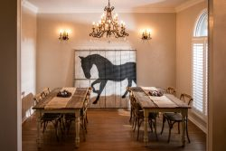 lovely dining room with two long wooden tables with chairs and chandelier; curtains have horse silhouette