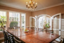beautiful dining room with large wooden table and chairs; large windows