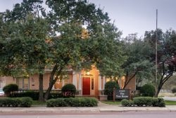 beautiful light red brick home with red door and white trim