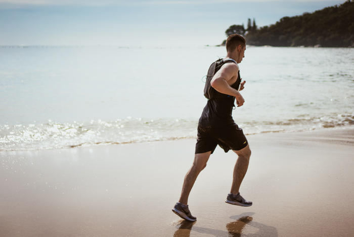 man in black shorts and shirt running on beach - physical