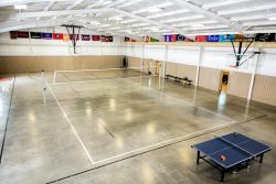 large gymnasium with lightly colored floors and volleyball net set up
