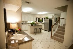 large kitchen with cream colored tile and staircase off to one side