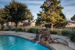 gorgeous outdoor pool with stacked stones water feature