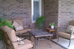 back porch of home with cushioned chairs and small table