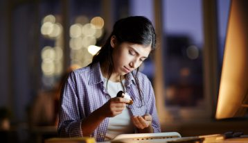 college age brunette girl taking pills at desk at night time - study drugs