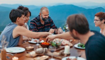 friends gathered for outdoor Thanksgiving or Christmas meal together - stressful