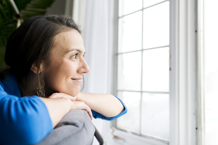 smiling woman looking out house window - transitional
