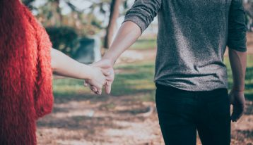 couple holding hands - pulling away from each other - spouse