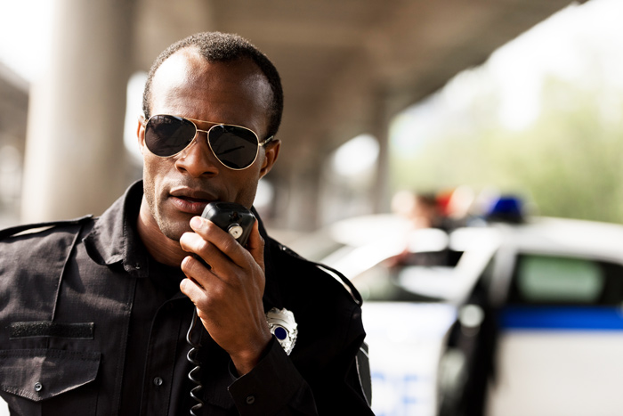 African American male police officer using CB radio - work
