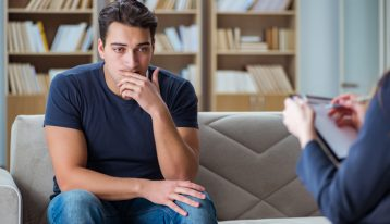young man in therapy session with counselor - CBT