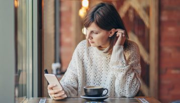 woman in cafe looking at cell phone - alcohol treatment