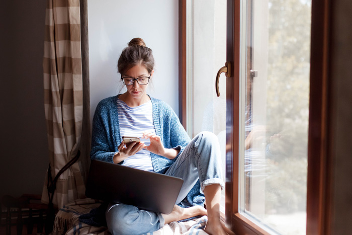 young woman in window nook using phone and laptop - time to enter recovery