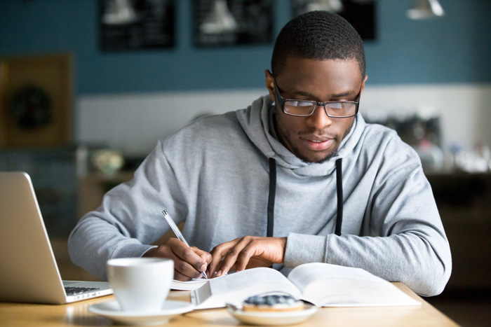 young handsome African American man doing college homework - high stress