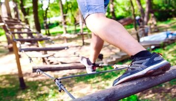close up of man doing a low ropes course in the woods - experiential therapy