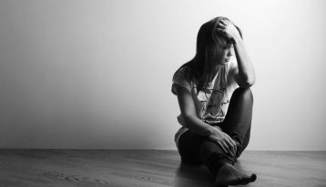 black and white image of young woman sitting on floor - depression and addiction