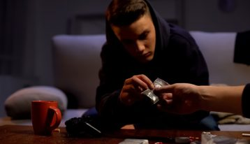 young man sitting in dark apartment with drugs and alcohol on coffee table - polysubstance misuse