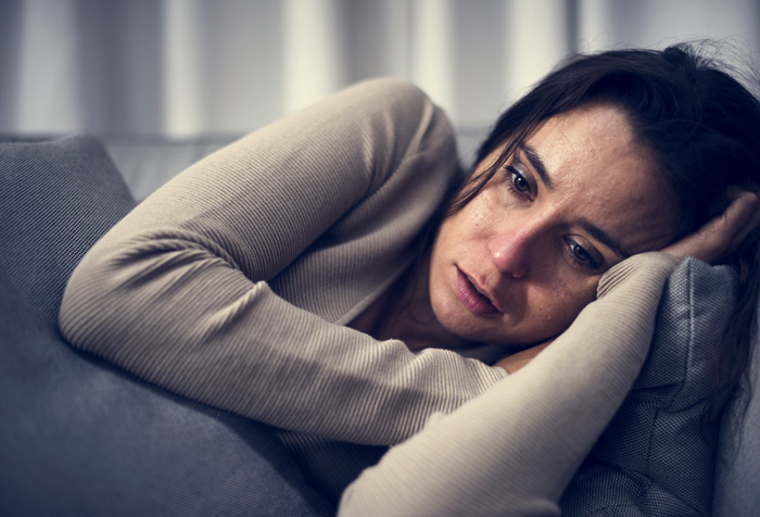 sad young woman on couch closeup - addiction causes
