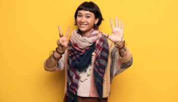 smiling young woman holding up hand sign for number seven on yellow background - residential treatment
