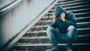 man sitting in hooded sweatshirt on stairs outdoors, visibly upset - spouse addicted