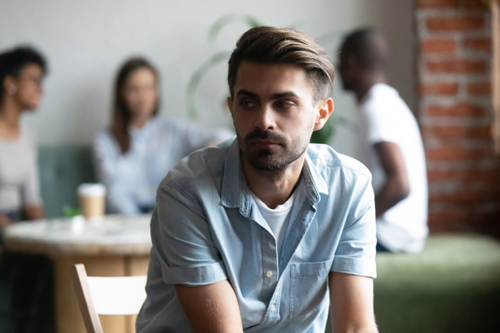handsome young man alone at cafe - negative thoughts