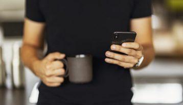 man holding a cup of coffee and dialing cell phone - pay for addiction treatment