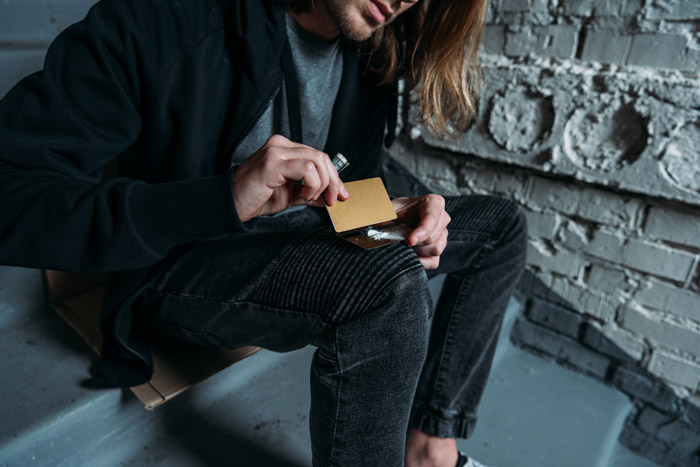 long haired man cutting lines of cocaine on a credit card - cocaine addiction