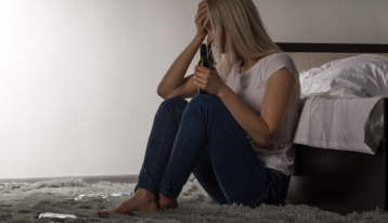 Girl sitting on floor with alcohol bottle - College